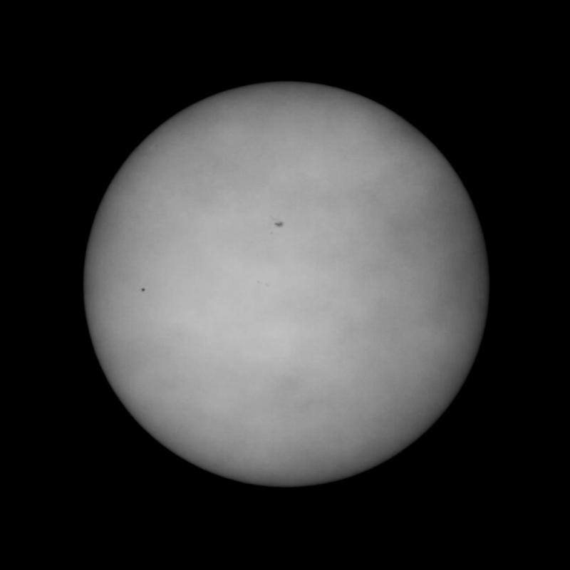 Merkur (links auf der Sonnenscheibe) währed des Transit aufgenommen mit Meade 102/ACHR500 Teleskop auf einer Losmandy G11 Montierung mit einem Intes Micro Herschelkeil, Baader Neutralfilter ND=3,0, Baader Solar Continuum Filter, Baader UV/IR Blocking Filter und einer Watec 120N+ Videokamera. Einige Wolkenfetzen, die das Bild zu diesem Zeitpunkt durchwanderten, sind gut zu erkennen. Im zentralen Bereich der Sonne sind eine Sonnenflecken sichtbar.